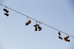 Shoes dangling on a electric cable over the street Royalty Free Stock Photos