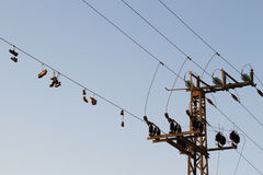 Shoes dangling on a electric cable over the street Royalty Free Stock Image