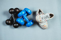 Shoes and dumbbells. On the rug are shoes and two pairs of dumbbells Royalty Free Stock Image