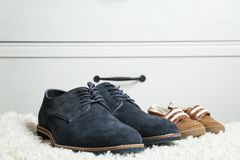 Shoes for father and son. On carpet Stock Photo