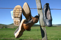 Shoes On Fence. Shoes hanging from barbed wire fence in the wilderness, New Zealand Stock Photos