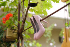 Shoes on Fence. Elegant wedding shoes hanging on fence in yard Stock Images