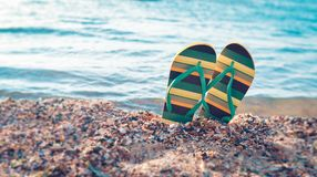 Shoes flip flops, beach accessories with yellow and green. On the beach of the ocean on the sand on holiday in summer for the advertising of the travel agency royalty free stock images
