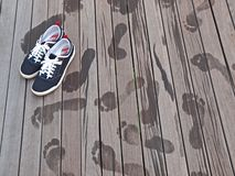 Shoes and Footprints. A pair of tracking shoes and footprints on wooden floor Royalty Free Stock Photos