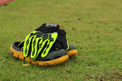 Shoes and gloves football in green grass. Stock Images