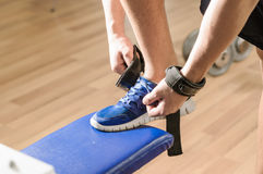 Shoes in gym. Young adult man is tying shoes Royalty Free Stock Photography