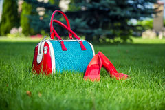 Shoes and handbag lay on the grass, women's shoes. Shoes and women's handbag lay on the grass, women's shoes Royalty Free Stock Photo