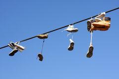 Shoes hanging on cable Royalty Free Stock Photography