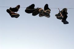 Shoes hanging on a cable Stock Photo