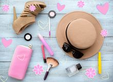 Shoes, hat, sunglasses, perfume, ink, eyeshadow, flowers, lipstick, makeup brush, blush, top view on a blue wooden background. 