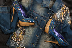 Shoes and jacket from denim fabric inlaid rhinestones lying on a black silk. Royalty Free Stock Photo