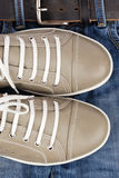 Shoes and jeans. Pair of sports summer shoes and jeans with a belt Royalty Free Stock Photography