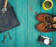 Shoes, jeans, camera, watch and vintage keys on the blue wooden. Travel concept - shoes, jeans, camera, watch and vintage keys on the blue wooden desk Royalty Free Stock Image