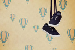 Shoes with laces hanging on wallpaper background with balloons. Royalty Free Stock Photo