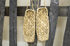 Shoes lacovia hang on the fence. Woven in handmade shoes of lime bast Royalty Free Stock Photography