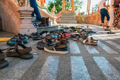 Shoes left at the entrance to the Buddhist temple. Concept of observing traditions, tolerance, gratitude and respect. Shoes left at the entrance to the Buddhist Royalty Free Stock Photo