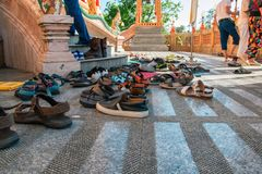 Shoes left at the entrance to the Buddhist temple. Concept of observing traditions, tolerance, gratitude and respect. Shoes left at the entrance to the Buddhist stock photos