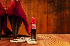 Shoes and lipstick and pearls. Red shoes with red lipstick and white pearls on wooden background Royalty Free Stock Photos