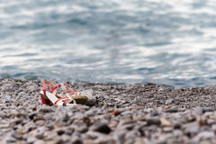 The shoes lying on the pebble beach Royalty Free Stock Photography
