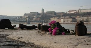 Shoes Memorial and Buda castle. Shoes memorial on the Danube Bank in Budapest to commemorate the murdered Jews during The World War II with view of castle in Royalty Free Stock Images