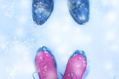 Shoes for men and women facing each other winter snow. Shoes for men and women facing each other winter snow Royalty Free Stock Photography