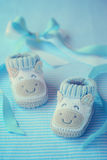 Shoes for newly born baby boy. Knitted baby shoes for boy on a blue background. Greeting card Stock Photography