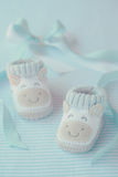Shoes for newly born baby boy. Knitted baby shoes for boy on a blue background. Greeting card Stock Image