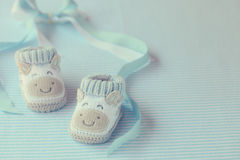 Shoes for newly born baby boy. Knitted baby shoes for boy on a blue background. Greeting card Royalty Free Stock Image