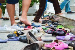 Shoes off. Visitors of a Buddhist temple in Bangkok taking their shoes off upon entering Stock Photos