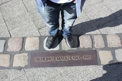 Shoes on the old berlin wall border. Man standing on the old border between east berlin and west berlin. The wall lasted from 1961 till 1989 Royalty Free Stock Images