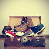 Shoes in an old suitcase. A pile of shoes in an old brown suitcase with a retro effect Stock Photography