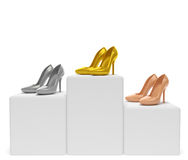 Shoes pedestal. Gold, silver, bronze woman shoes (high heels stilettos) stand on winner podium as symbol of award ceremony of the best successful shoe company or Stock Photos