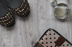 Shoes, perfume, purse. Composition, female shoes with multi-colored large crystals, perfume in a glass bottle and a purse on a wooden background Stock Photo