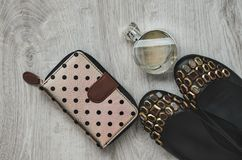 Shoes, perfume, purse. Composition, female shoes with multi-colored large crystals, perfume in a glass bottle and a purse on a wooden background Stock Images