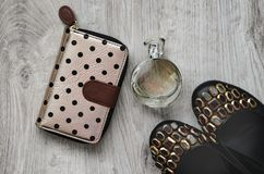 Shoes, perfume, purse. Composition, female shoes with multi-colored large crystals, perfume in a glass bottle and a purse on a wooden background Royalty Free Stock Images
