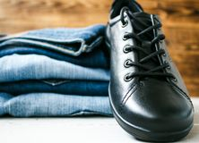 Shoes on a pile of jeans on a wooden background. A shoes on a pile of jeans on a wooden background Stock Images