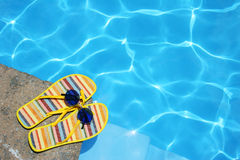 Shoes By Pool. Bright Flip-flops and sunglasses by swimming pool Stock Photography