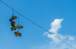 Shoes on the power line. Old shoes hanging on the high-voltage wire on blue sky backgroun Stock Images