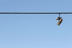Shoes on power lines. Urban scene, worn tennis shoes hanging from a power line against clear blue sky. plenty of copyspace Royalty Free Stock Image