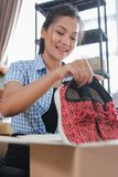 Shoes product ready to be shipped. Young woman packing of shoes on carton boxes to be shipped in her office stock image