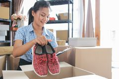 Shoes product ready to be shipped. Young woman packing of shoes on carton boxes to be shipped in her office stock photography