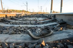 Shoes at the railway tracks of the sunset outside the city in nature, the ties and rails stretching into the distance Stock Photography
