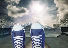 Shoes relaxing feet in front of dramataic sky clouds and mountain trees Royalty Free Stock Photo
