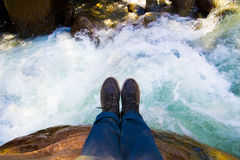 Shoes with a river as background Stock Images