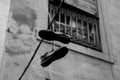 Shoes in the rope. Street photography - shoes hanging on a wire in the old side of the city Stock Photos