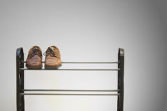 Shoes on shoe rack. A lone pair of shoes shot in studio setting placed on a shoe rack stock image