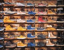 Shoes in the shop window. Lots of different men`s and women`s shoes sneakers, boots, plimsolls on the showcase in market. Image stock image