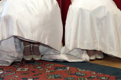 Shoes and skirts of two brides sitting next to each other Royalty Free Stock Photos
