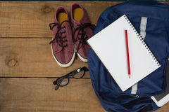 Shoes, spectacles, book, pencil, digital tablet and schoolbag on wooden table. Close-up of shoes, spectacles, book, pencil, digital tablet and schoolbag on Stock Photos