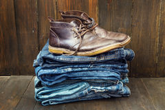 Shoes on the stack of jeans Stock Images